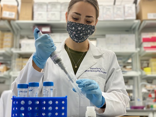 Woman in a lab filling test tubes